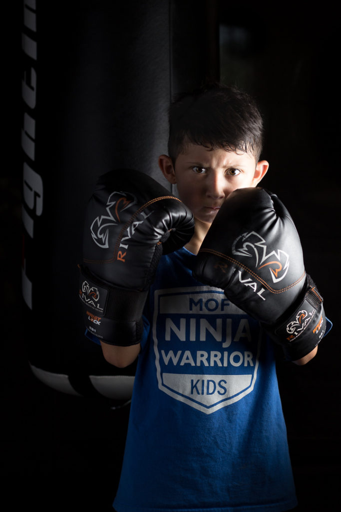 Child in boxing gloves posing in front of punching bag